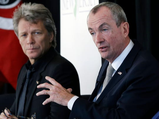 Jon Bon Jovi, left, listens as Philip Murphy addresses a gathering in Newark in 2016.
