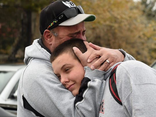 Kelly Young hugs his son Logan after a student was