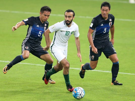FILE - In this Tuesday, Sept. 5, 2017 filer, Saudi Arabia's Mohammed Al Sahlawi, center, runs with the ball against Japan's Yuto Nagatomo, left, and Japan's Gen Shoji during the 2018 World Cup group B qualifying soccer match between Saudi Arabia and Japan in Jiddah, Saudi Arabia. (AP Photo, File)