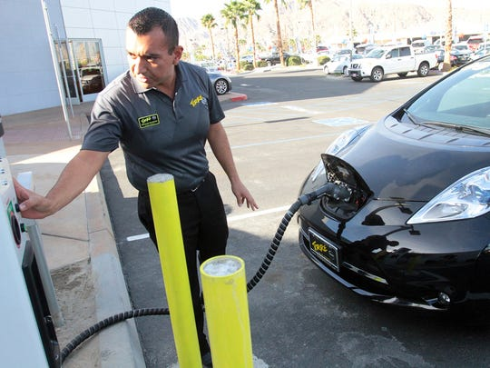 Torre Nissan general manager Marcelino Maldonado demonstrates the new Nissan Electric Vehicle Quick Charger as he powers up a Nissan Leaf electric vehicle outside the dealership in La Quinta, California on Jan. 23, 2014.