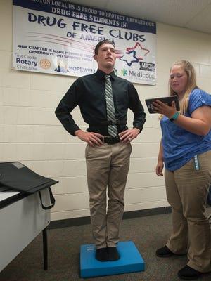 Amanda Keeton, right, an Adena athletic trainer, tests Huntington junior quarterback Elijah McCloskey's balancing during a multi-faceted concussion test.
