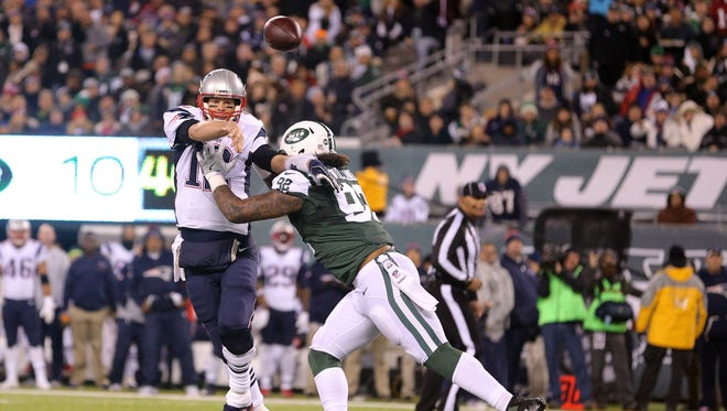 New England Patriots quarterback Tom Brady (12) throws the ball as New York Jets defensive end Leonard Williams (92) defends during the second quarter at MetLife Stadium.