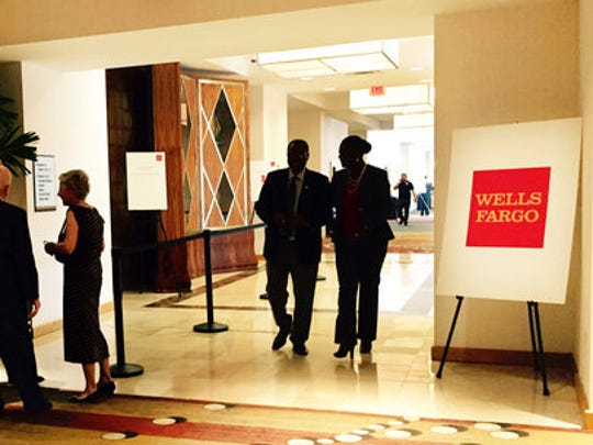 People stand and walk near the entrance to the Wells Fargo shareholders meeting in Ponte Vedra Beach, Fla., Tuesday, April 25, 2017. Wells Fargo's top management and board of directors apologized to investors and faced a series of protesters Tuesday at the first big shareholder meeting since a scandal over sales practices led to an executive shake-up, fines and a dented reputation.