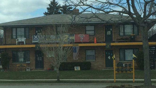 Banners supporting the Green Bay Packers and Wisconsin Badgers adorn the apartment building at 2032 S. Oneida St. in Ashwaubenon on Monday, April 11, 2016.