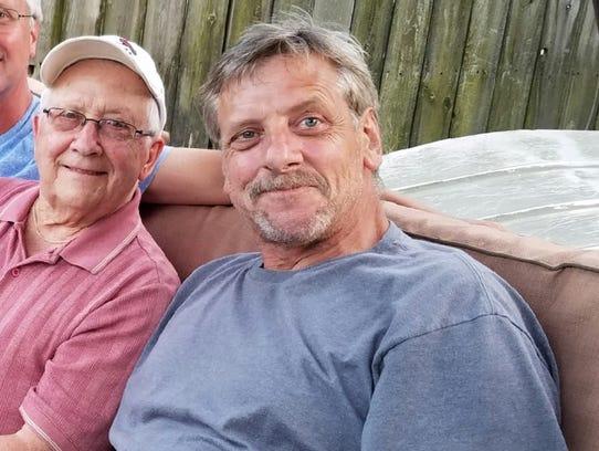 Jeffrey Kempf sits with his father, Tom Kempf. Jeffrey