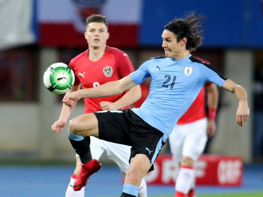 Austria's Marcel Sabitzer, left, challenges Uruguay's Edinson Cavani, during an international friendly soccer match between Austria and Uruguay in Vienna, Austria, Tuesday, Nov. 14, 2017. (AP Photo/Ronald Zak)
