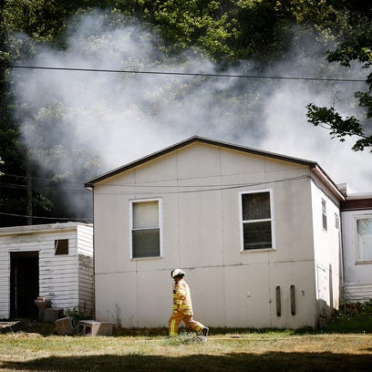 A Webb Mills Fire Department tanker truck dumps water into a mobile pond as smoke billows from the home at 1 Sitzer Road in Pine City Saturday afternoon.