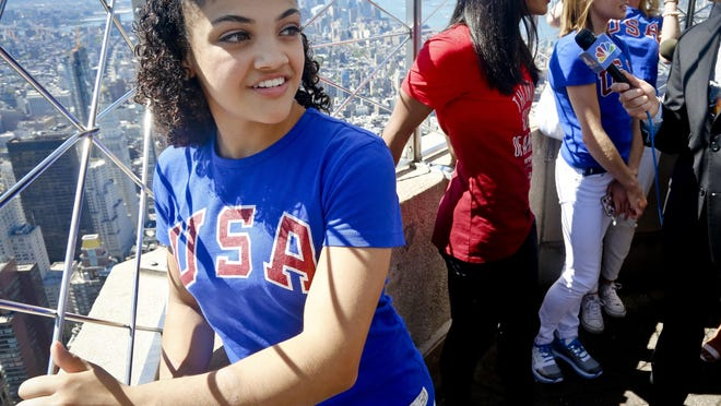 U.S. gymnast Laurie Hernandez, back from the Rio Olympics, looks out from atop the Empire State Building while teammates are interviewed in New York, Tuesday, Aug. 23, 2016.