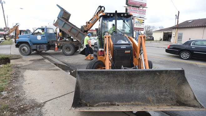 A crew from the Zanesville Water Maintenance Department finishes up a project on Maple Avenue in Zanesville on Wednesday. The city is considering combining the water maintenance and sewer maintenance departments.
