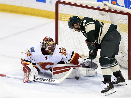 Calgary Flames goalie Niklas Backstrom (32) blocks a shot by Minnesota Wild right wing Jason Pominville (29) during the first period on April 9 in St. Paul.