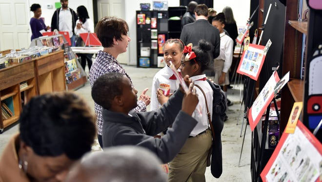"""Midtown Public Charter School fifth- and sixth-grade students show off their comic book artwork from """"The Mighty Midbot"""" to visitors Wednesday during a release party at Offbeat. Midtown partnered with ELSEWorks, the entrepreneurship program of the Else School of Management at Millsaps College to create the comic book."""