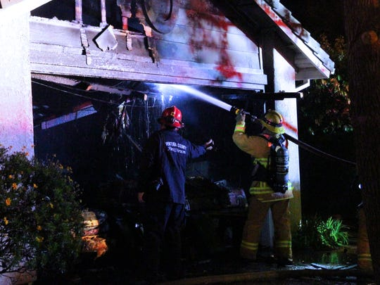 Crews with the Ventura County Fire Department battled a fire in the garage of a Camarillo home on Saturday night that displaced three people.
