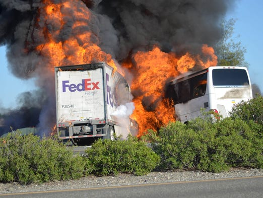 Massive flames devour both vehicles just after a crash Thursday when a FedEx tractor-trailer crossed a grassy freeway median in Northern California and slammed into a bus carrying high school students on a visit to a college.