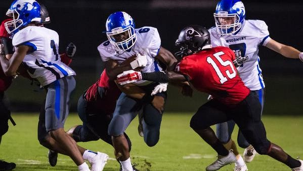 Woodmont's Gionn Klugg (6) gets sandwiched by  Hillcrest defenders Friday night.