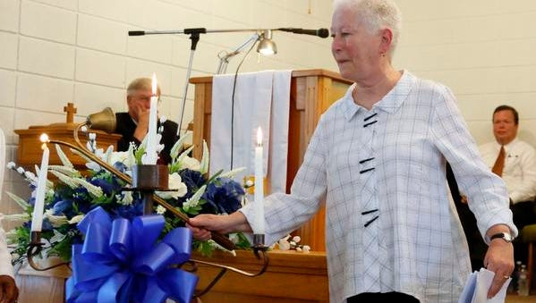 """In this June 15, 2014 photo, Rita Schwerner Bender, widow of Michael Schwerner, lights a candle during a commemorative service for her husband and the two other men killed in the """"Mississippi Burning"""" case, at Mt. Zion United Methodist Church in Philadelphia, Miss. Michael Schwerner, Andrew Goodman and James Chaney are going to be posthumously awarded the Presidential Medal of Freedom on Monday, Nov. 24, 2014, but the honor is not sitting well with some of their relatives."""