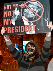 A protester holds up a sign in opposition of Donald Trump's presidential election victory, Thursday, Nov. 10, 2016 at Jefferson Square Park in Louisville Ky.