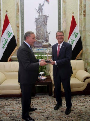 Visiting U.S. Defense Secretary Ash Carter, right, receives a gift from his Iraqi counterpart Khaled al-Obeidi during their meeting at the Ministry of Defense, Baghdad, Iraq, Monday, April 18, 2016.
