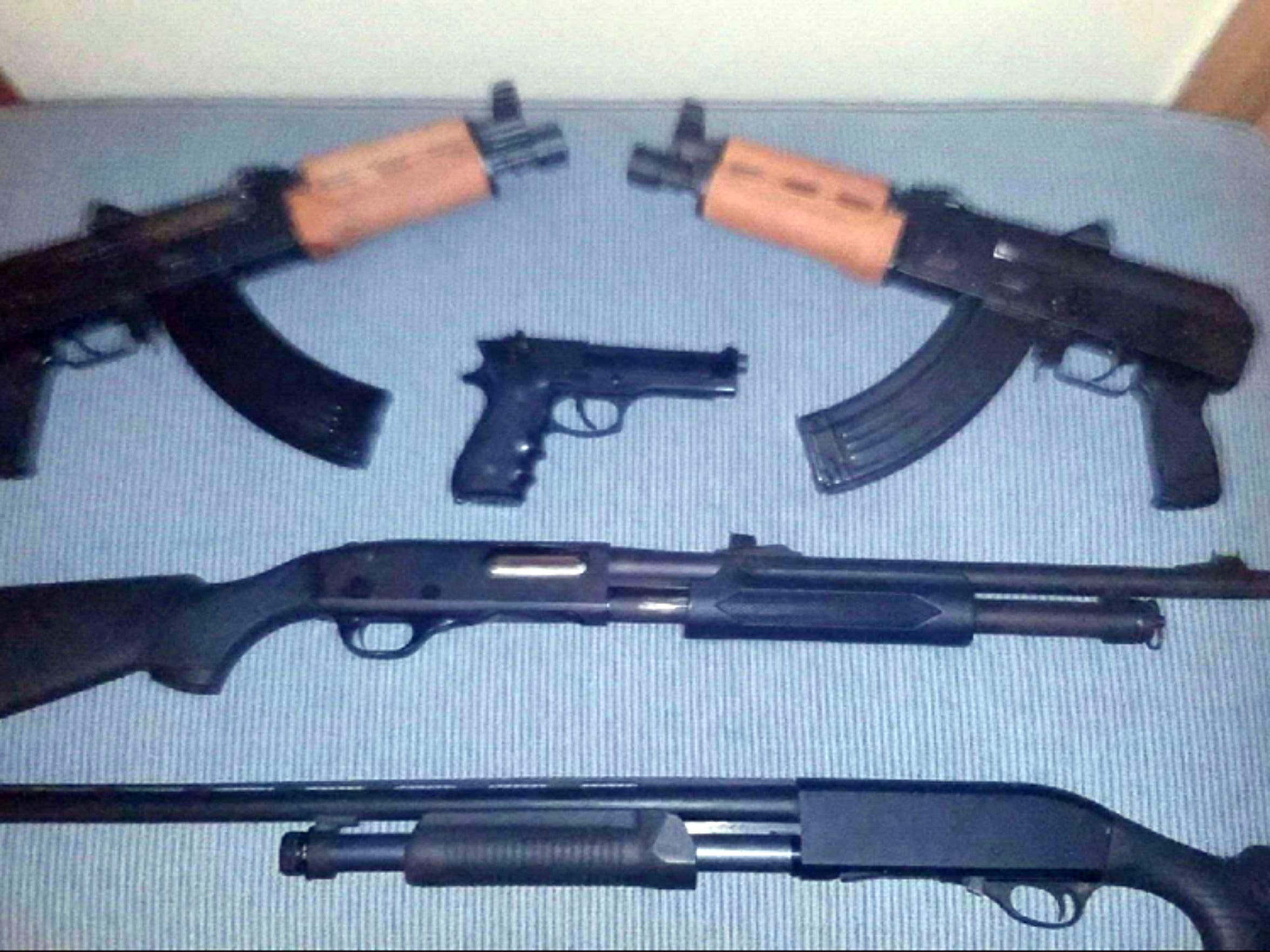 Guns in the collection of former gang member Rico include mini-AK semi-automatic pistols, top, which he bought privately without a background check. He bought the 9-millimeter Beretta handgun and the pump-action rifles at a gun show in Black River Falls, Wis. through private vendors, also without a background check.