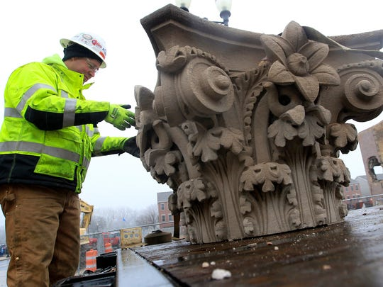 Miron construction employee Jason Hardy secures the cap that was removed from the stone pillars of a historic bank building on Main St. on Dec. 23 in Menasha.