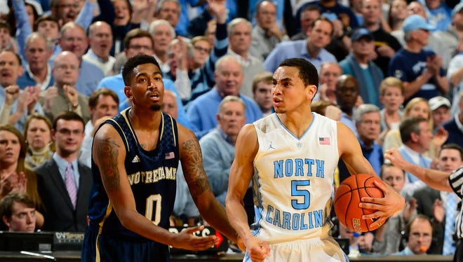 North Carolina Tar Heels guard Marcus Paige (5) is fouled by Notre Dame Fighting Irish guard Eric Atkins (0) in the last minute of the game. The Tar Heels defeated the Fighting Irish 63-61 at Dean E. Smith Student Activities Center.