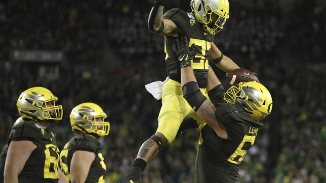 Oregon running back Cyrus Habibi-Likio is hoisted by former Ducks offensive lineman Shane Lemieux after scoring a touchdown against California last season at Autzen Stadium.