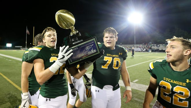 """Sycamore Aviators linebacker Garrett Boyd (32) hoists the """"Battle of the Skies"""" trophy after the 21-7 win against the Mason Comets, Friday, Sept. 8, 2017, at Sycamore Junior High School in Montgomery, Ohio."""