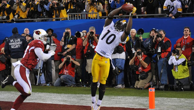 Pittsburgh Steelers wide receiver Santonio Holmes (10) catches a touchdown pass in front of Arizona Cardinals safety Aaron Francisco (47) in the fourth quarter of Super Bowl XLIII at Raymond James Stadium.