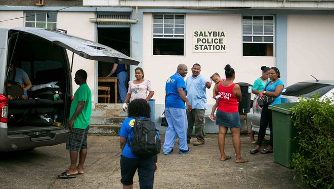 Dr. Rey Agard chats with villagers at the Salybia Police Station where they begin to set up a clinic asking all to spread the word of their arrival.