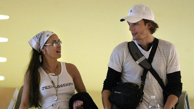 Demi Moore and Ashton Kutcher chat as they walk inside The Westin Diplomat Hotel during a Kabbalah Convention in 2004.