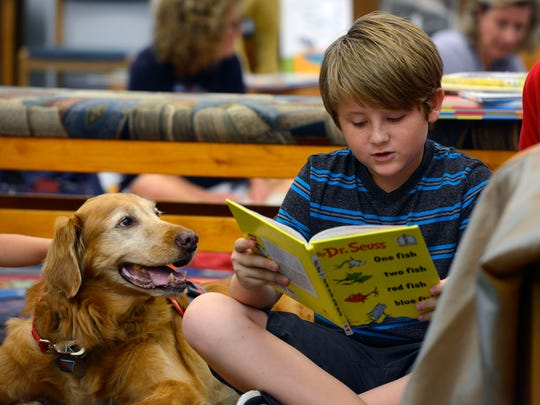 Jackson Camargo,10, reads to Molly Saturday morning during the READ (Reading Education Assistance Dog) to the Dogs program at the Southwest Branch Library. Molly is retiring from the program after 10 years on the job.
