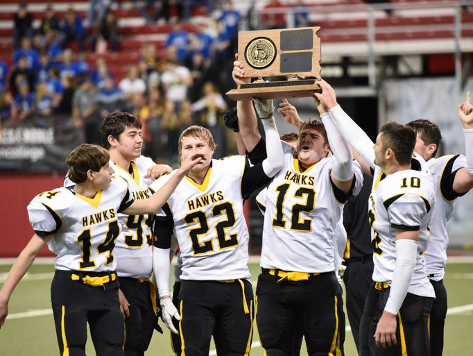 Players on Colman-Egan hoist the state championship