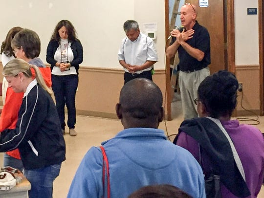 Father Lopez Delfino (center left) from San Marcos, Guatemala prays with Father Roger DiBuo (right) of St. Elizabeth Ann Seton before they venture onto buses to Philadelphia from DiBuo's parish in Bear.