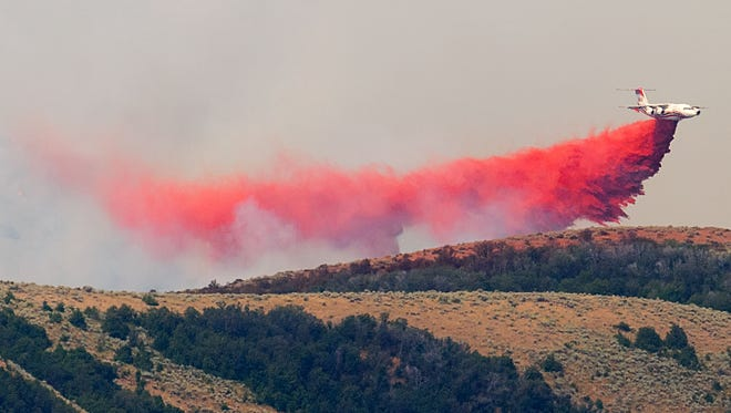A plane aids in firefighting efforts on the ridgeline of a wildfire Thursday, Aug. 4, 2016, near Plymouth, Utah. Officials say more than two dozen large wildfires are burning in the West.