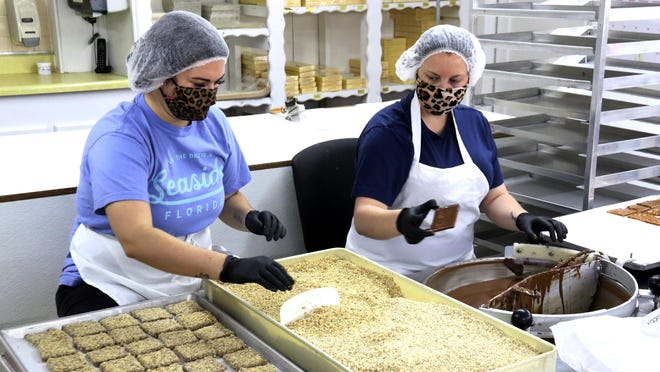Khloe Heinrich, left, and Brandi Kizer create a toffee candy for customers at Kopper Kettle Candies, 6300 Alma Hwy., Tuesday, July 7, 2020. Kopper Kettle has been making  chocolates and confections since 1925 and invites the public to visit the factory and watch how the candies are made.