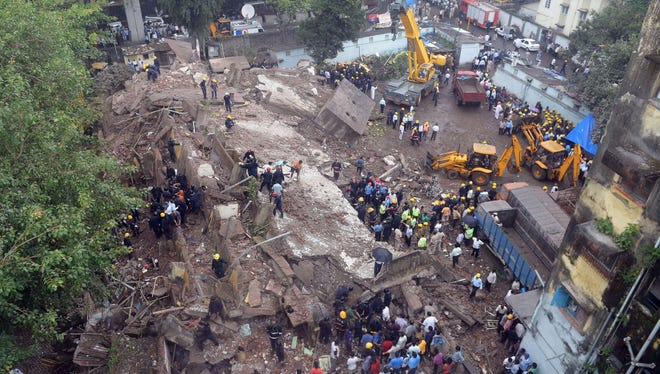 Firefighters and rescue workers are seen working at the site of the building collapse in Mumbai on Friday.