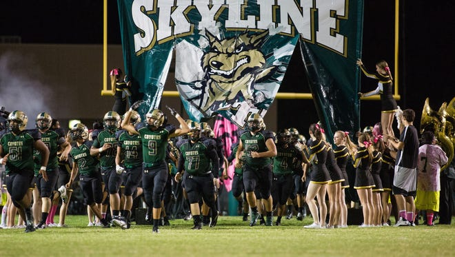 The Skyline High School football team runs through their banner at the opening of a Skyline home game against the Desert Ridge Jaguars on Oct. 10, 2014 in Mesa.
