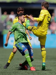 Columbus Crew midfielder Pedro Santos, right, makes contact with the face of Seattle Sounders midfielder Alex Roldan, left, in the first half of an MLS soccer match, Saturday, May 5, 2018, in Seattle. After video review, Santos was given a red card on the play. (AP Photo/Ted S. Warren)