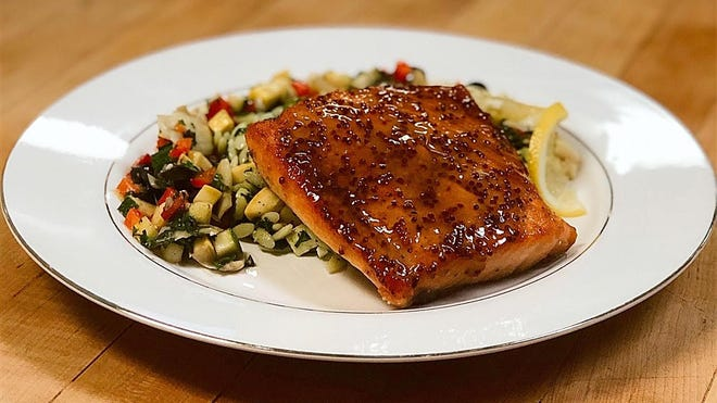 Honey-glazed salmon with roasted vegetable medley is on the catering menu at C'es Si Bon in Lake Park.