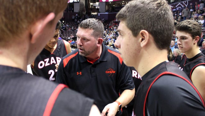Ozark High School boys basketball coach Mark Schweitzer (center) talks to the Tigers before the start of the second half of a Greenwood Blue and Gold Tournament game against Fair Grove at JQH Arena on Dec. 27, 2016.