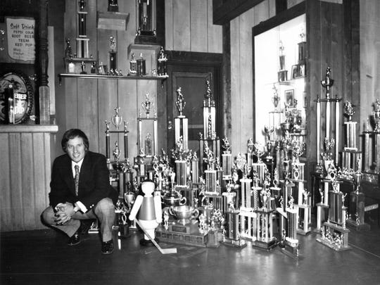 Little Caesar's owner Mike Ilitch with trophies won by teams he sponsors circa 1976.