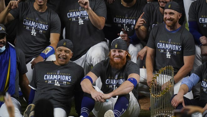 Los Angeles Dodgers manager Dave Robert and third baseman Justin Turner pose for a group picture after defeating the Tampa Bay Rays 3-1 to win the World Series in Game 6 Tuesday, in Arlington, Texas.