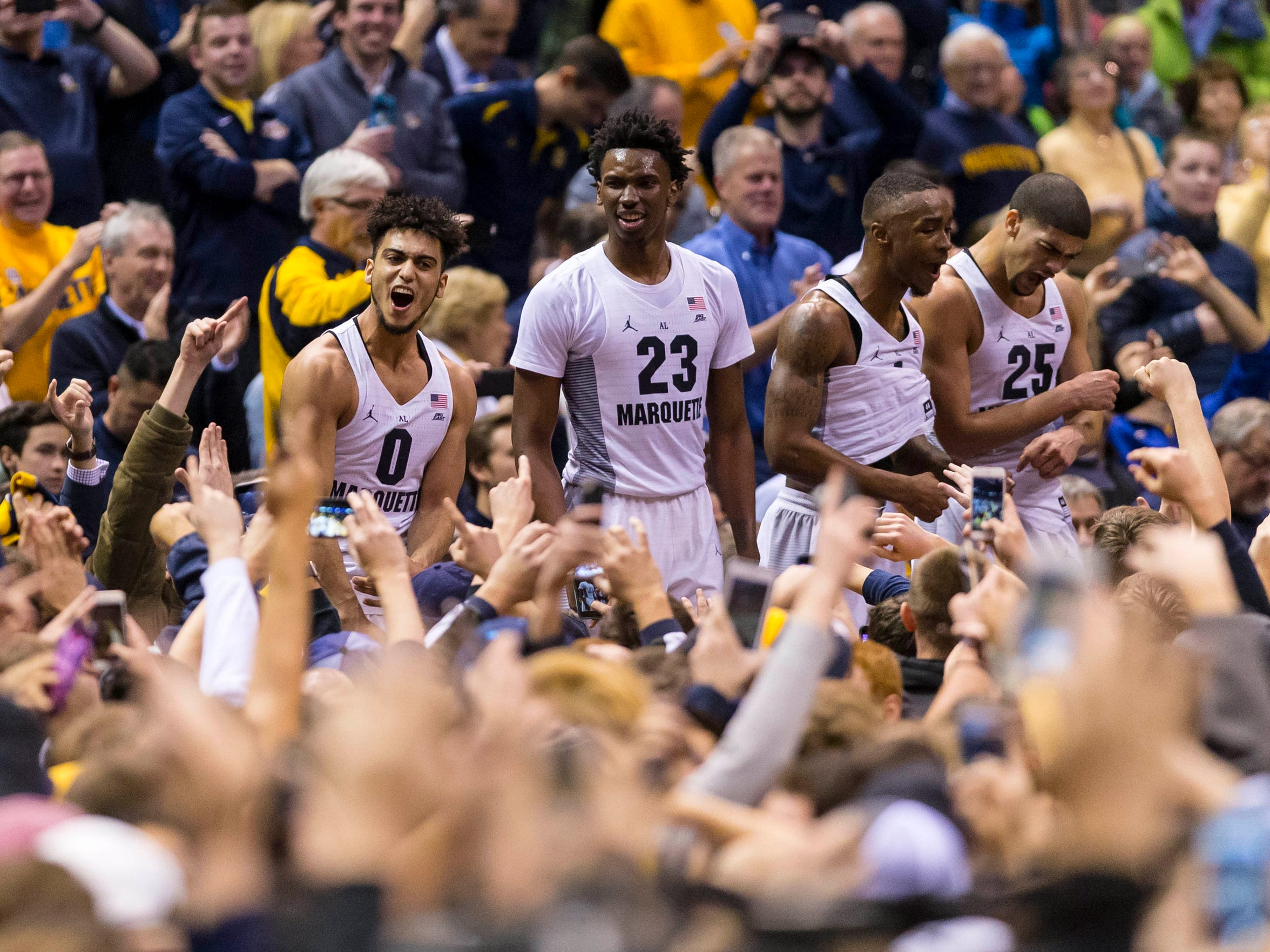 Marquette players celebrate with fans after defeating