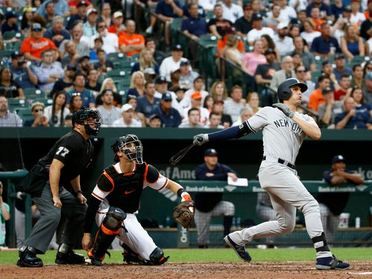 New York Yankees' Greg Bird, right, watches his grand slam in front of Baltimore Orioles catcher Caleb Joseph and home plate umpire Jim Reynolds during the third inning of a baseball game Wednesday, July 11, 2018, in Baltimore.