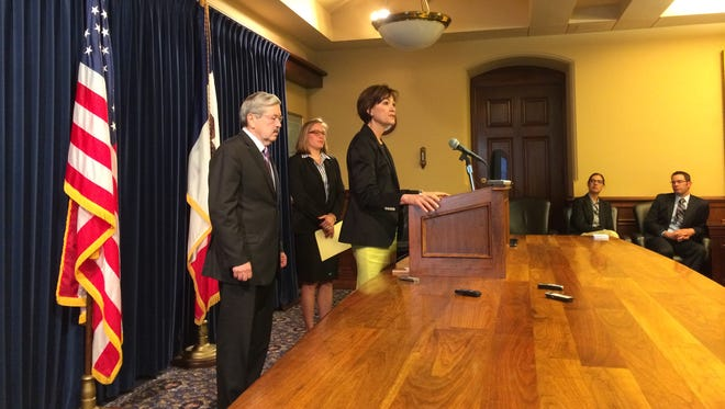 Lt. Gov. Kim Reynolds, at podium, describes the upcoming Iowa Arts Summit while Gov. Terry Branstad and Director of Cultural Affairs Mary Cownie look on.