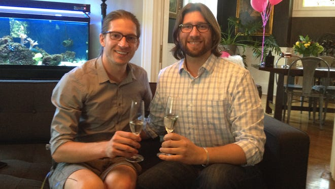 Jake Miller (left) and Craig Bowen drink champagne at their home near Downtown Indianapolis after becoming the first same-sex to be married in Marion County.