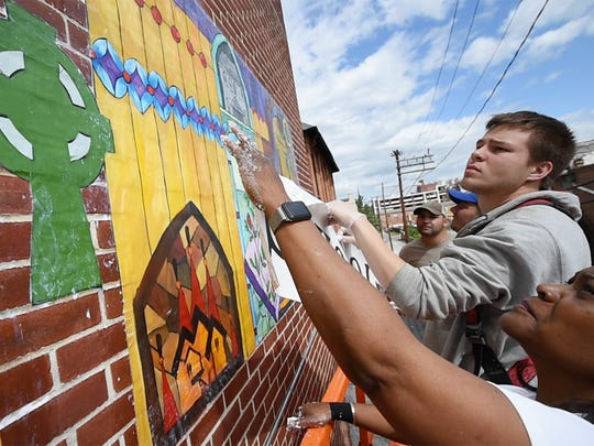 From the left, Kyler Jelonek, a former student, and artist Ophelia Chambliss work with others installing the mural on St. Patrick Catholic School in York.