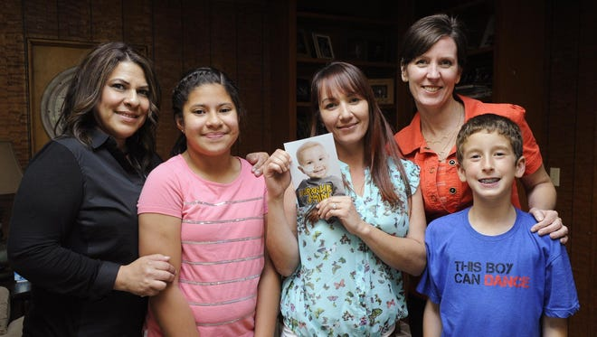 Diana Garcia, 45, left, her daughter Samantha, 10, Aimee Grijalva, 41, and Shannon Montemurno, 42 and her son, Sean, 10, are organizing a head-shaving fund raiser in September for the St. Baldrick Foundation which funds research for childhood cancers. Grijalva, center, holds a photo of her son, Matthew Pierce, who died when he was 2 years old in 2013.