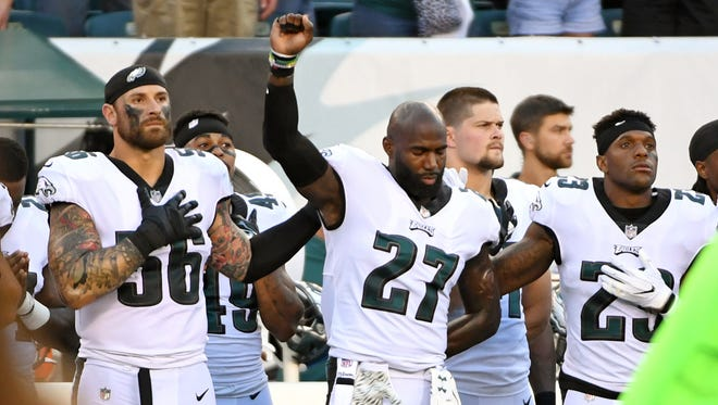 Philadelphia Eagles strong safety Malcolm Jenkins (27) is joined by defensive end Chris Long (56) and free safety Rodney McLeod (23) during the national anthem against the Miami Dolphins at Lincoln Financial Field.