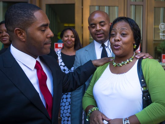 Shanesha Taylor, gets support from her attorney, Benjamin Taylor (left) and the Rev. Jerrett Maupin following her settlement with the Maricopa County Attorney's Office on Friday, July 18, 2014. Taylor must complete a diversion program to have the child-abuse charges dropped. She was charged in March for leaving her children in the car in Scottsdale applying for a job.