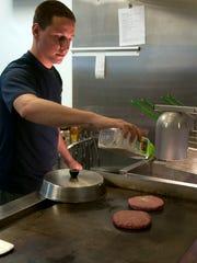 Dennis Trendel seasons some burger patties while working at the Hidden Beach Bar at Schrock's Marina in Danbury Township.